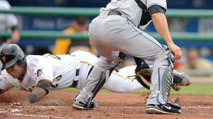 Pirates catcher Robinzon Diaz slides home as Mets catcher Omir Santos waits for a throw in the second inning yesterday.