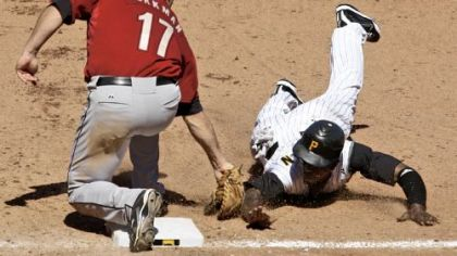 Nyjer Morgan dives back to first base as Houston's Lance Berkman reaches to apply the tag off a throw from catcher Humberto Quintero in the ninth inning. Morgan was called safe.