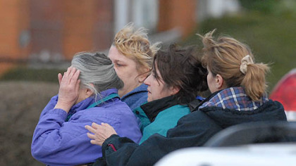 Family members of shooting suspect Richard Poplawski -- including women identified by a friend as his grandmother, far left, and mother, second from right -- comfort each other along Fairfield Street in Stanton Heights yesterday.