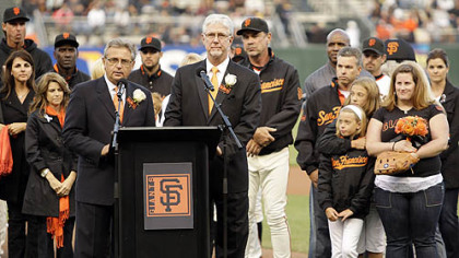 Giants announcers Mike Krukow, right of podium, and Duane Kuiper lead a pre-game tribute to Sue Burns, a part owner of the Giants who lost her battle with cancer.