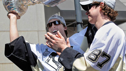 Penguins goalie Marc-Andry Fleury holds up the Stanley Cup as he rides with captain Sidney Crosby along Grant Street.