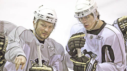 Sergei Gonchar, left, explains a drill to teammate Evgeni Malkin during hockey practice at Southpointe yesterday. The Penguins take on the Carolina Hurricanes in Game 1 of the Eastern Conference finals tonight at Mellon Arena.