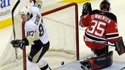 Sidney Crosby, left, celebrates after scoring a goal against New Jersey Devils goaltender Scott Clemmensen during the first period of last night's game.