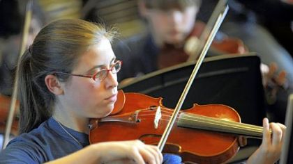 "Violinist Lara Konefal-Shaer rehearses for a student production of ""Les Miserables."""