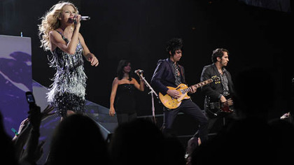 Taylor Swift with the band in the background.
