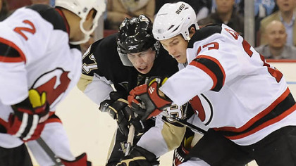 Sidney Crosby battles for loose puck with the Devils David Clarkson in the third period.