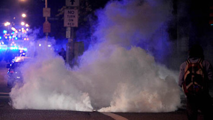 Riot police lob gas grenades Friday night following a student protest near Schenley Plaza.