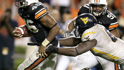Auburn linebacker Craig Stevens, left, intercepts a pass and returns it for a touchdown past West Virginia offensive line Selvish Capers, right, in last night's game.