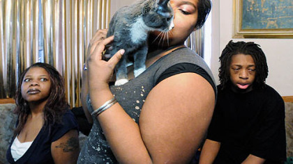 "Brittany Boyer, 16, nuzzles her kitten, Silver, after school with her mother, Darlenea Adetona, left, and brother, Michael ""M.J."" Adetona, 15. Mrs. Adetona and her three children (daughter Ashley Boyer, 18, is not pictured) recently moved in with a relative."