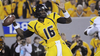 West Virginia quarterback Jarrett Brown runs past Cincinnati defensive lineman Dan Giordano for a first-quarter touchdown last night in Cincinnati.