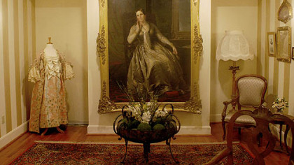 The parlor displays a photo of a family relative, a countess and a restored gown that she wore.