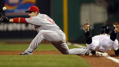 Pirates shortstop Ronny Cedeno dives for first base as Reds first baseman Joey Votto reaches for the throw from third baseman Scott Rolen in the second inning. Cedeno was safe as the ball got past Votto.