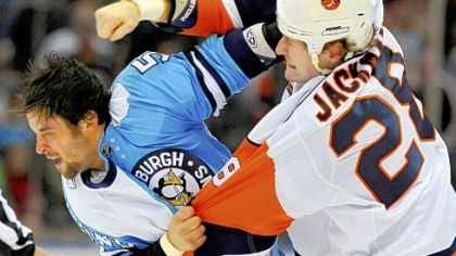 The Islanders' Tim Jackman and the Penguins' Deryk Engelland fight in the first period yesterday in Uniondale, N.Y.  Both players were given penalties.