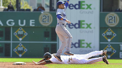 Dodgers shortstop Juan Castro jumps to catch the ball as the Pirates first baseman/outfielder Garrett Jones slides safely into second base.