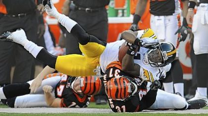 Steelers kick returner Stefan Logan is dragged out of bounds by the Bengals&#039; Roy Williams.