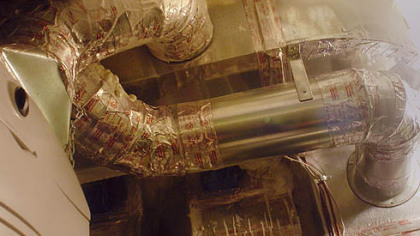 The heating system uses metal ductwork sealed with tape. Sprayed insulation can be seen at the top.