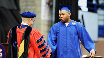 Sam Ashaolu accepts his diploma from Duquesne University President Charles Dougherty.