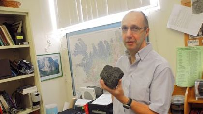 Dr. Ian Skilling, volcanology professor at the University of Pittsburgh, shows a rock from an Icelanic volcano.