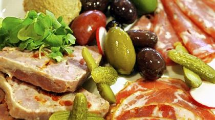 Le Pommier serves house-made country pate and chicken liver mousse with cured meats and assorted olives.