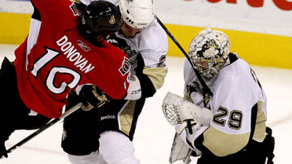 Senators forward Shean Donovan is checked by Penguins defenseman Nathan Guenin as Penguins goaltender Marc-Andre Fleury (29) holds the puck during the second period.
