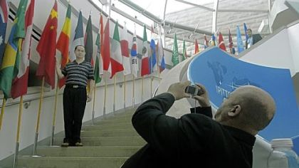 Chinese G-20 delegate Huiyu Zheng is photographed with his country's flag on the steps at Phipps Conservatory by a colleague, Omar Bouzid of Morocco. There was a flurry of activity at Phipps yesterday as it prepared to host events for the summit.