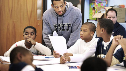 Pitt basketball player Chase Adams works with students at University Prep in the Hill District on an exercise to write a defining statement about themselves. Adams, coach Jamie Dixon and other players are involved with the community program working with children at the school.
