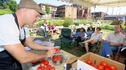 Jamie Moore, Eat'n Park's director of sourcing and sustainability, demonstrates canning tomatoes at the Braddock Community Garden last month.