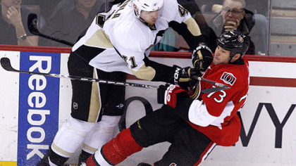 Senators forward Jakko Ruutu is checked by Penguins defenseman Martin Skoula during the first period.