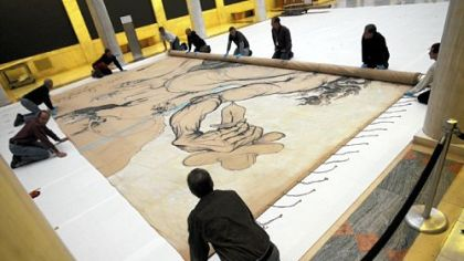 Staff at the Carnegie Museum of Art roll up Dali&#039;s 1942 curtain &quot;Theseus Minotaur&quot; after inspecting it yesterday.
