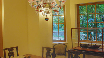 A Murano glass chandelier hangs over the dining room table. Dr. Anti built the whaling boat in the glass case.