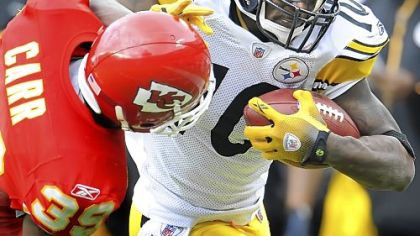 Steelers Santonio Holmes fights off a tackle by Chiefs defensive back Brandon Carr.