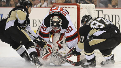 Chris Kunitz and Sidney Crosby try to push the puck past Devils goalie Martin Brodeur in Saturday's loss.