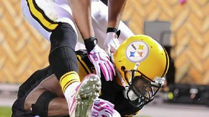 Hines Ward hurdles over Mewelde Moore, who scores in the first half against the Chargers last night at Heinz Field.