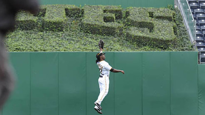 Pirates outfielder Andrew McCutchen leaps to catch a ball in center field.