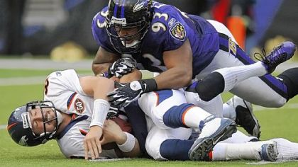 Broncos quarterback Kyle Orton lies on the field after being sacked in the fourth quarter by Baltimore Ravens cornerback Chris Carr (partially obscured) and defensive tackle Dwan Edwards during Sunday&#039;s game in Baltimore.