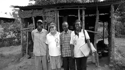 George McGee, second from left, with Stephen Omondi Okongo, Stephen's brother Dennis and a CFCA social worker outside Stephen's old mud house ...