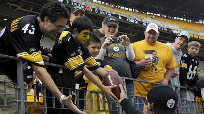 Ethan Kahn, 10, of Chappaqua, NY., receives a football from Steelers quarterback Ben Roethlisberger prior to the Sunday's game.  For Ethan and his father Oren Kahn, left, this is the first time they have been to a Steelers' game.