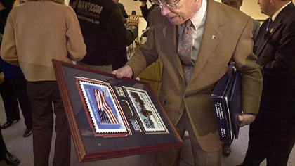 "Jack Foley, a member of ""Easy Company,"" looks at his plaque and holds a U.S. flag following ceremonies in the Penn Hills Muncipal Building in 2001."