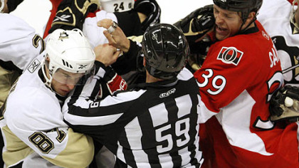 Penguins forward Sidney Crosby throws a punch at Senators defenseman Matt Carkner during.