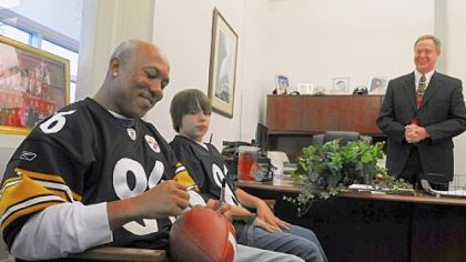 Pittsburgh Steelers receiver Hines Ward signs autographs with eighth-grader David Grove and Principal Robert Gallagher at Freedom Area Middle School. David got to spend time with Ward as winner of an NFL contest to encourage exercise.