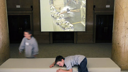 "Cao Fei's video ""Whose Utopia,"" part of the 2008 Carnegie International, ""Life on Mars,"" is projected into an unused museum entryway that these children play in front of at the Carnegie Museum."